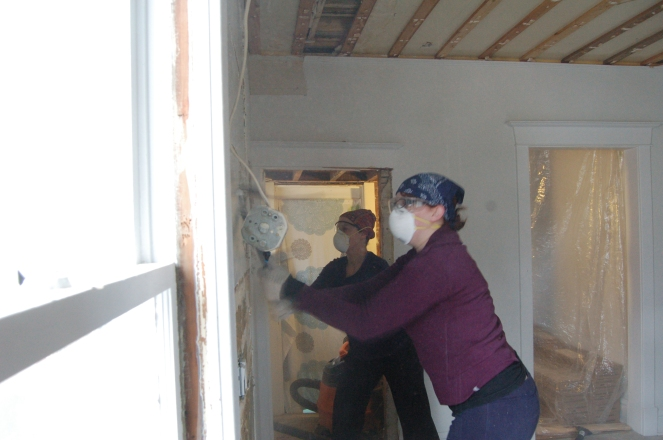 Photo of two women wearing dust masks and using crowbars to remove a plaster wall.