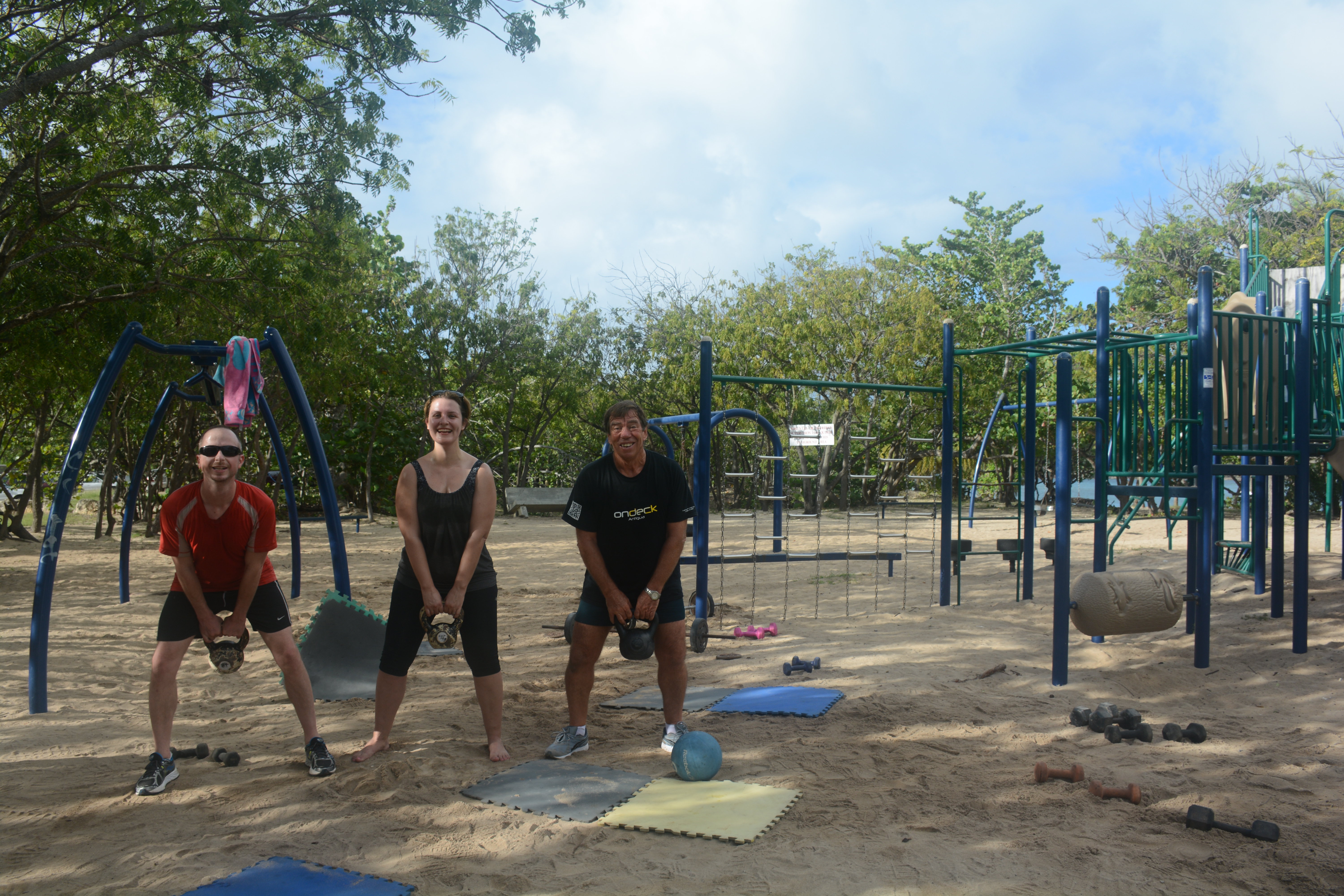 Three people on a beach with kettlebells.