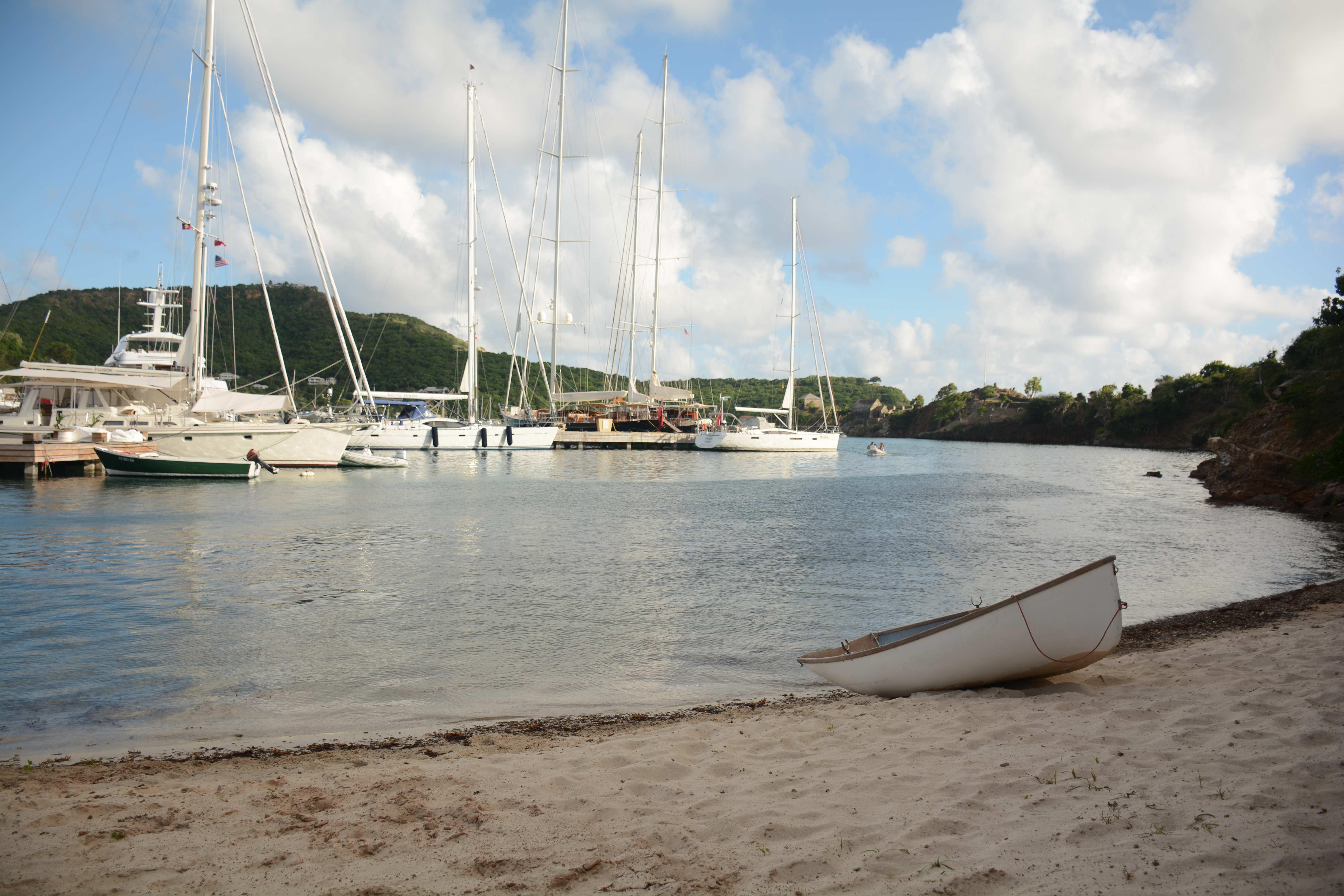 image of beach with sailboats docked in the background.